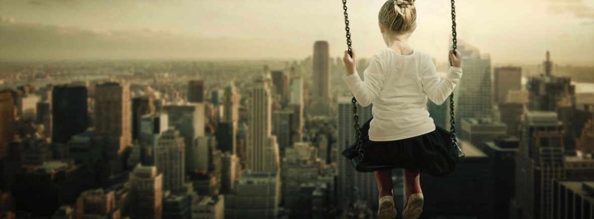 A girl on a swing looks down upon a big city.