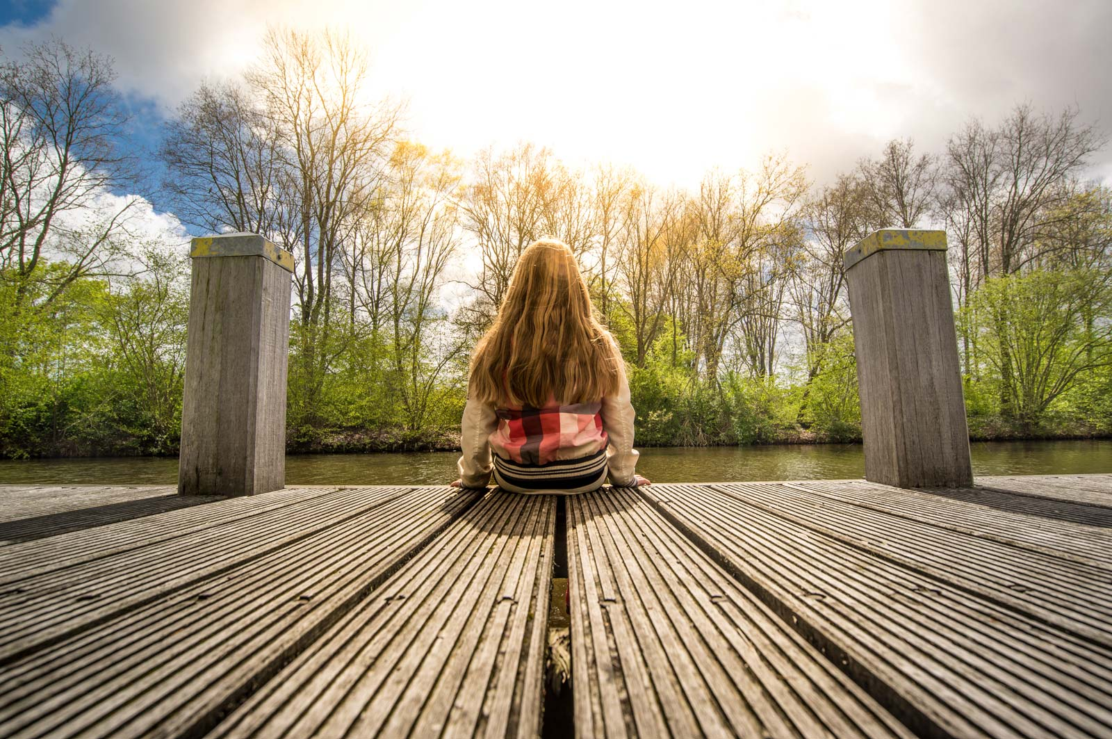 A girl sits on a pier staring into the water.